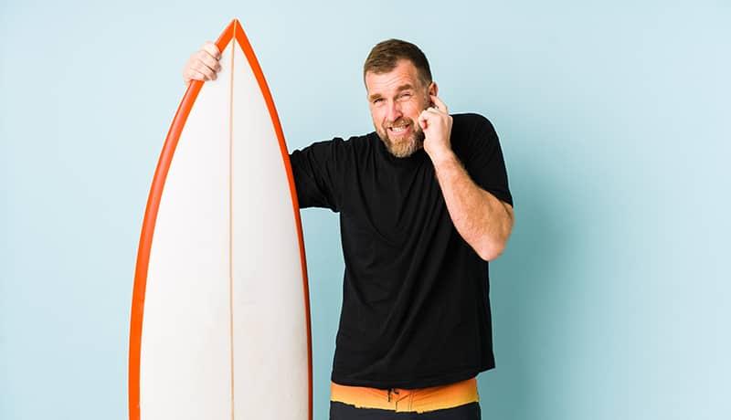 Mann mit Surfbrett fasst sich ans Ohr, weil er an einer Gehörgangsexostose leidet.