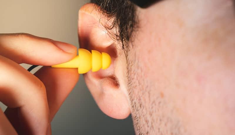 Mann, der regelmäßig seine Ohren reinigen sollte, mit Ohrstöpsel