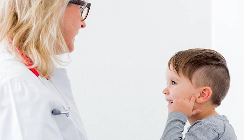 Junge mit Ohrenentzündung bei der HNO-Untersuchung.