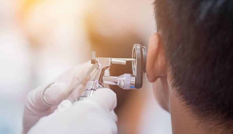 Mann lässt sich im Rahmen der Ohrenpflege von Arzt untersuchen.