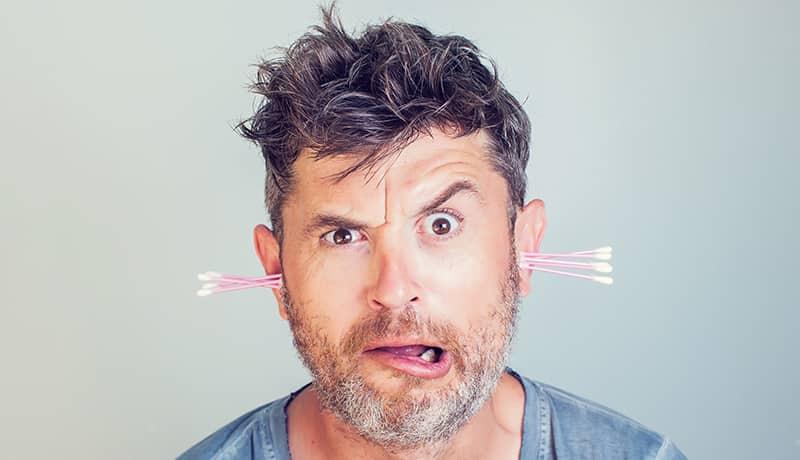 Mann mit Wattestäbchen im Ohr fragt sich, ob sie sich zum Ohrenschmalz entfernen eignen.