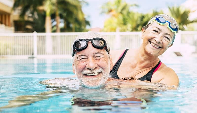 Älteres Paar im Schwimmbad mit Wasser im Ohr.